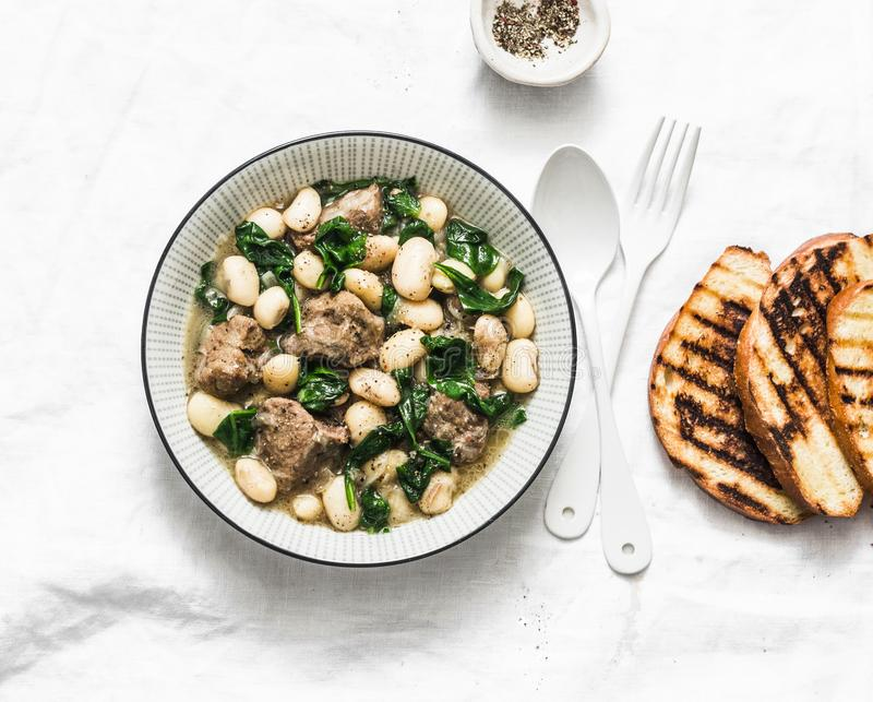 Rindfleisch, Bohnen, Spinatseintopfgericht auf einem hellen Hintergrund K?stliche selbst gemachte Komfortnahrung stockfoto