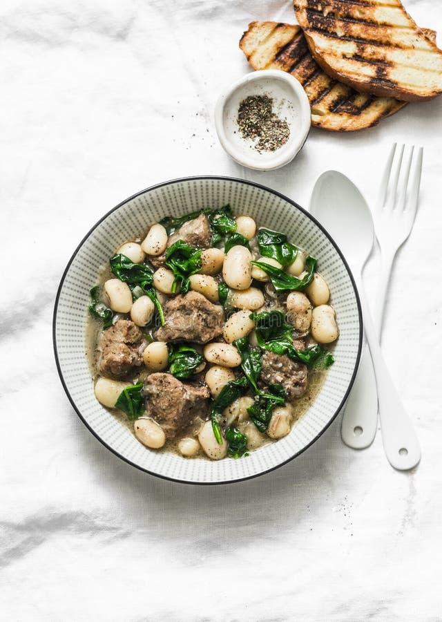 Rindfleisch, Bohnen, Spinatseintopfgericht auf einem hellen Hintergrund K?stliche selbst gemachte Komfortnahrung stockbilder