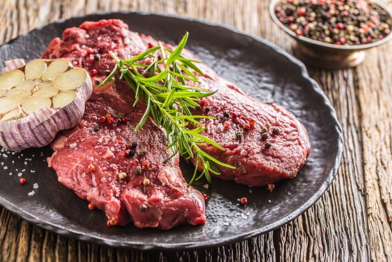 Rindfleisch meeat Rippe-Augensteakespritrosmarinsalz und -pfeffer auf Schwarzblech stockfotos