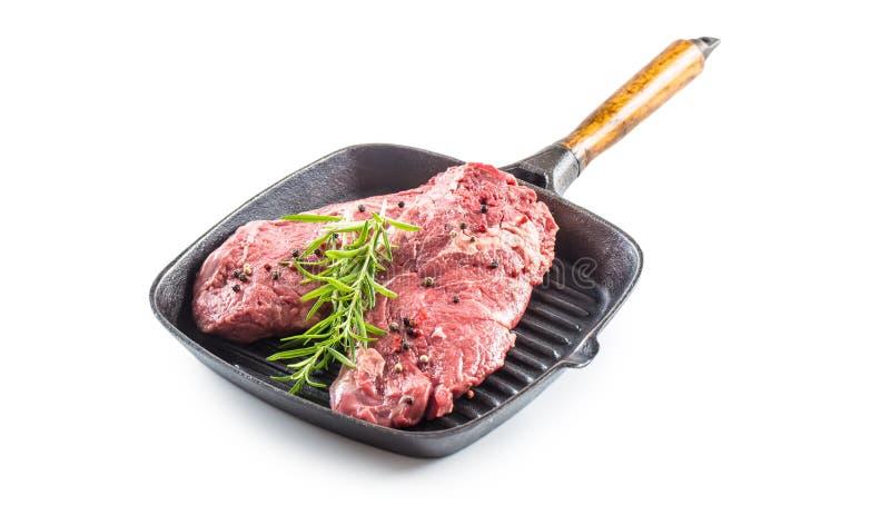 Rindfleisch meeat Rippe-Augensteakespritrosmarinsalz und -pfeffer in der Grillwanne lokalisiert auf Weiß stockbild