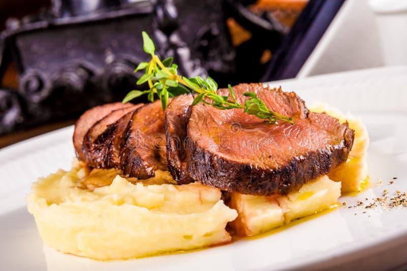 Rindfleisch mit Kartoffelpürees auf weißer Platte stockfotografie