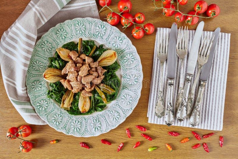Rindfleisch spitzt Mangoldgemüse und gegrillte Zwiebeln stockfoto