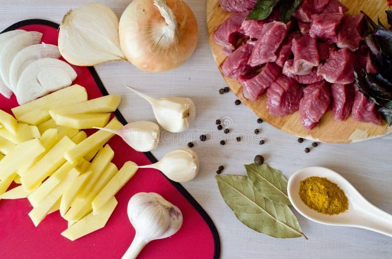 Rindfleisch wird in Stücke und abgezogene Kartoffelscheiben und -zwiebeln, Knoblauch und Löffelgewürze auf weißem Hintergrund ges stockfoto