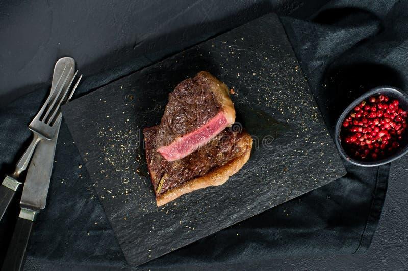 Rindfleischrumpsteak briet seltenes Schwarzer Hintergrund, Draufsicht stockfoto
