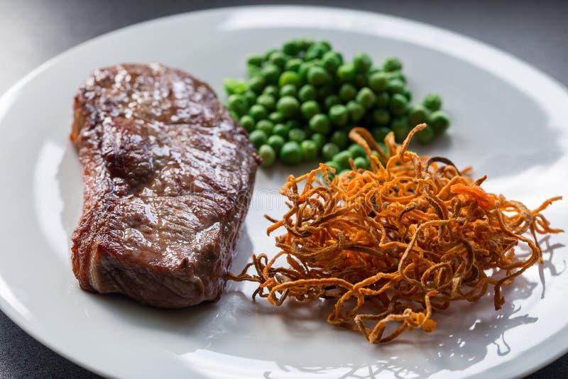 Rindfleischsteak mit grünen Erbsen und Süßkartoffel stockbilder