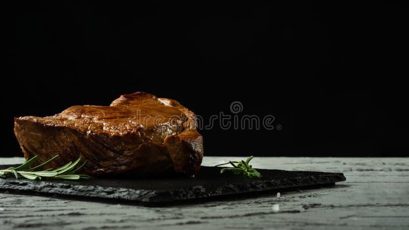 Rindfleischsteak mit Rosmarin auf einem schwarzen Hintergrund mit offenem Raum für Textentwurfs- oder -restaurantmenüs Horizontal stockfotografie