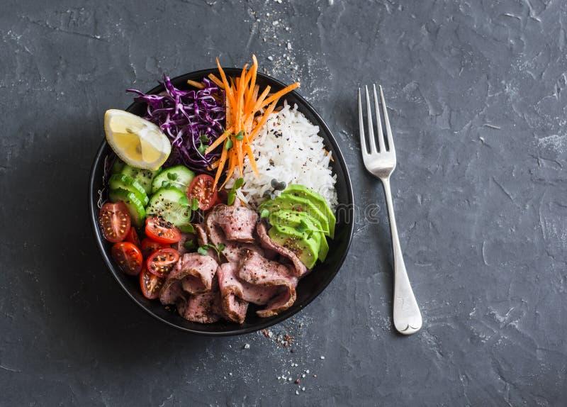 Rindfleischsteak, -reis und -gemüse treibt Schüssel an Gesundes ausgeglichenes Lebensmittelkonzept Auf einem dunklen Hintergrund lizenzfreie stockfotos