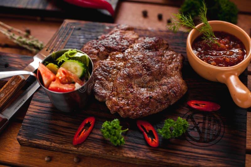 Rindsteak mit Chili auf einem Holztisch lizenzfreies stockfoto