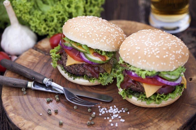 Rinforzi gli hamburger su un bordo di legno con le spezie aromatiche immagine stock libera da diritti