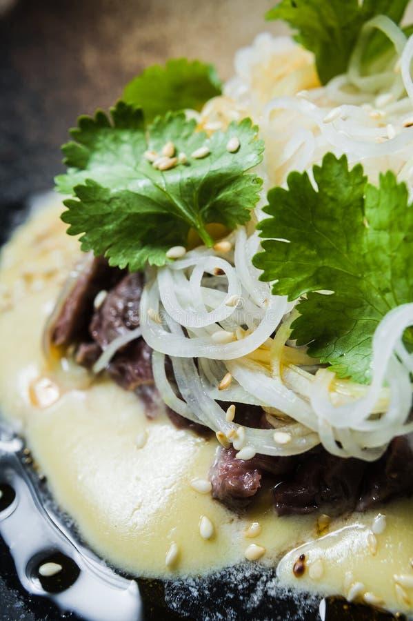 Rinforzi il filetto con le tagliatelle di vetro e del salsa, fondo scuro immagine stock libera da diritti