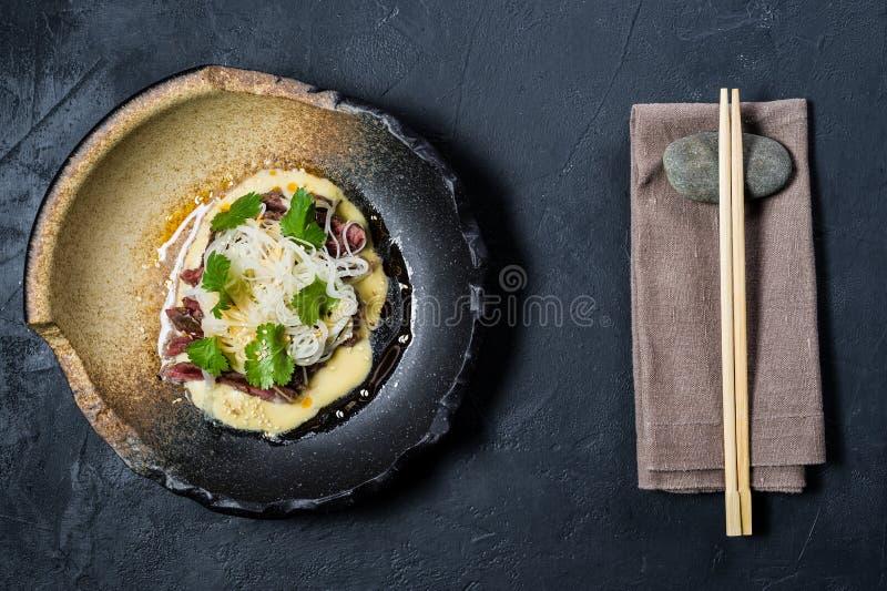 Rinforzi il filetto con le tagliatelle di vetro e del salsa, fondo scuro immagini stock libere da diritti