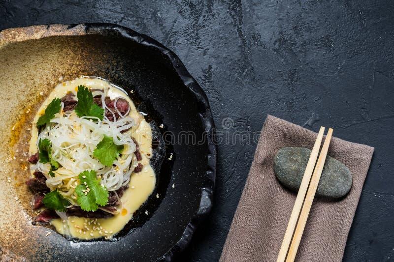 Rinforzi il filetto con le tagliatelle di vetro e del salsa, fondo scuro fotografia stock