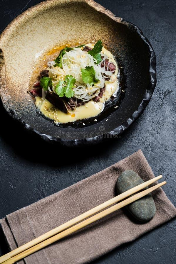 Rinforzi il filetto con le tagliatelle di vetro e del salsa, fondo scuro immagini stock
