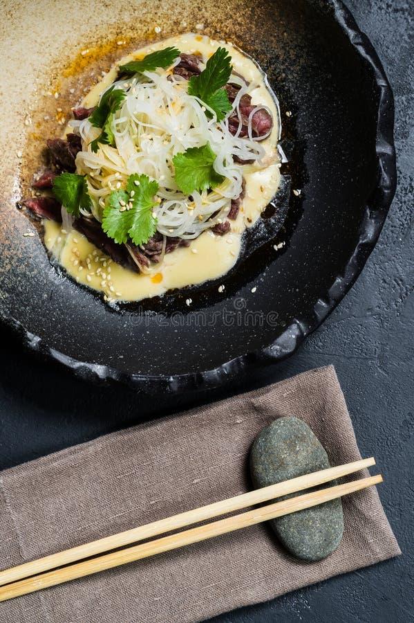 Rinforzi il filetto con le tagliatelle di vetro e del salsa, fondo scuro fotografia stock libera da diritti