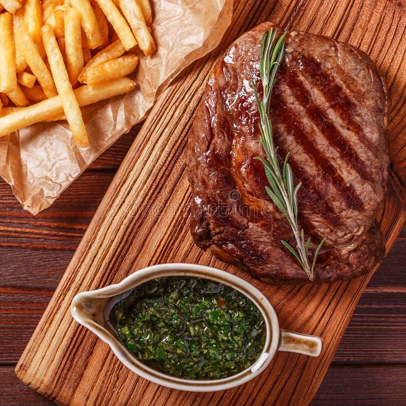 Rinforzi la bistecca del ribeye del barbecue con la salsa di chimichurri ed il francese fri fotografie stock libere da diritti