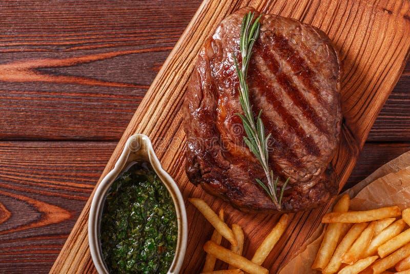 Rinforzi la bistecca del ribeye del barbecue con la salsa di chimichurri ed il francese fri fotografia stock libera da diritti