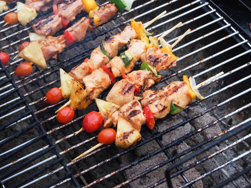 Rinforzi la carne di maiale ed il BBQ del pollo sulla griglia fotografia stock libera da diritti