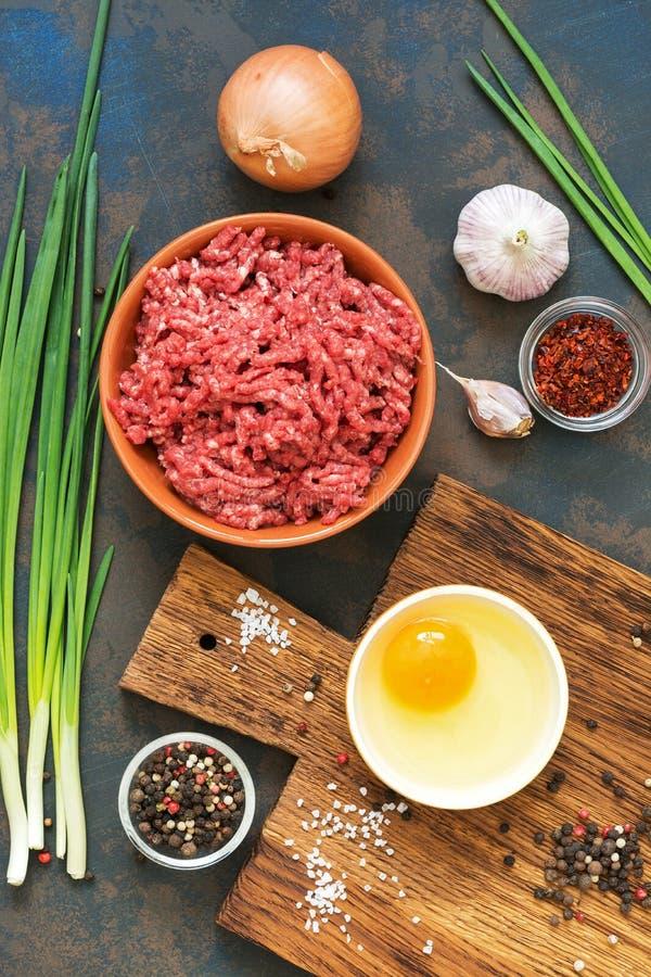 Rinforzi la carne tritata cruda, l'uovo crudo, le spezie, l'aglio, la cipolla verde, tagliere Ingredienti per la cottura le cotol fotografie stock