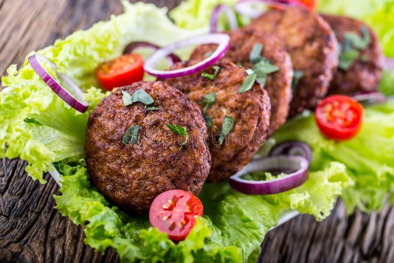 Rinforzi le cotolette delle polpette degli hamburger con la cipolla del pomodoro dell'insalata della lattuga sul bordo di legno fotografie stock
