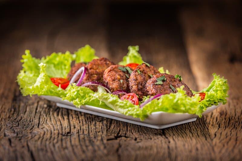 Rinforzi le cotolette delle polpette degli hamburger con la cipolla del pomodoro dell'insalata della lattuga sul bordo di legno immagine stock libera da diritti