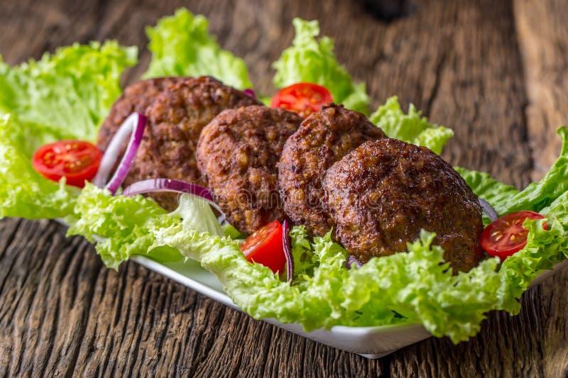 Rinforzi le cotolette delle polpette degli hamburger con la cipolla del pomodoro dell'insalata della lattuga sul bordo di legno immagini stock libere da diritti