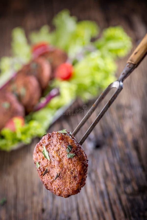 Rinforzi le cotolette delle polpette degli hamburger con la cipolla del pomodoro dell'insalata della lattuga sul bordo di legno immagini stock