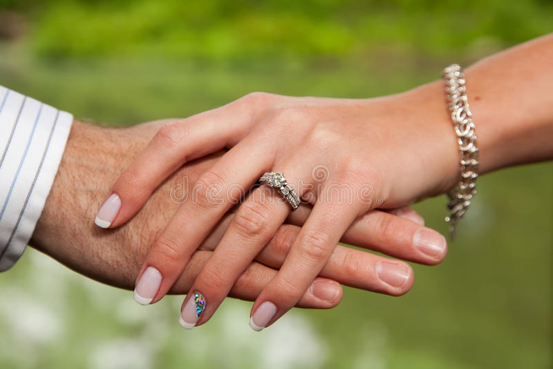 Ring. Engaged couple hold hands showing the new diamond ring on the woman's finger royalty free stock photo