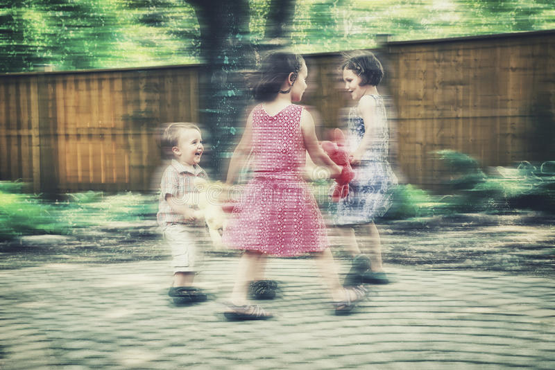 Ring Around the Rosie Motion Blur - Retro. Girls and boys are holding hands together in a circle playing a game of ring around the rosie holding colorful plush stock photos