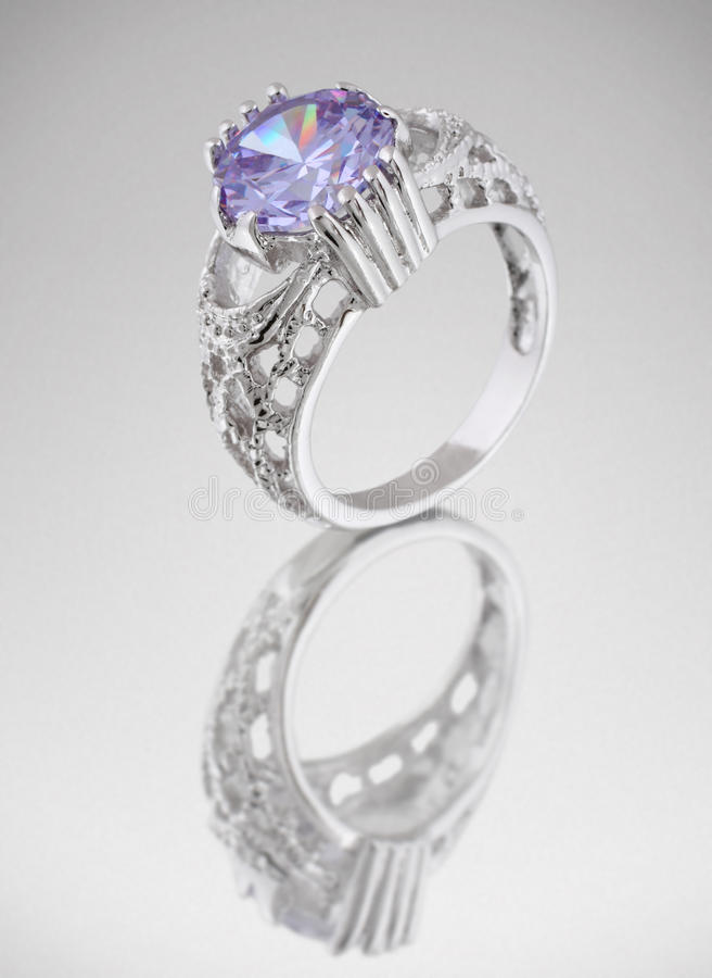 Ring with blue gem on grey royalty free stock images
