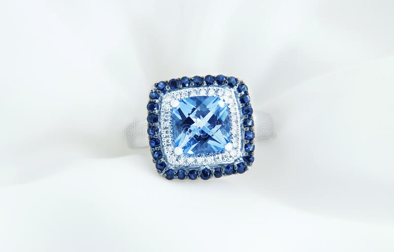 Ring with blue topaz and diamonds on soft white background stock photos