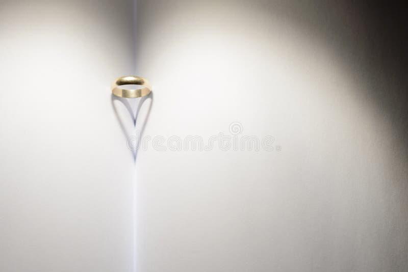 Ring die een hart van schaduw op een boek vormen stock afbeeldingen