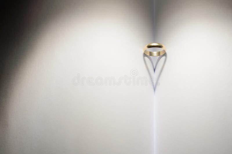 Ring die een hart van schaduw op een boek vormen royalty-vrije stock foto's
