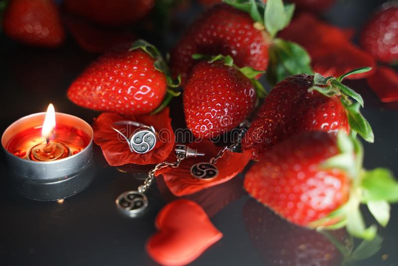 Ring and earrings with the symbol of bdsm lying among the strawberries on the black table top view royalty free stock photos