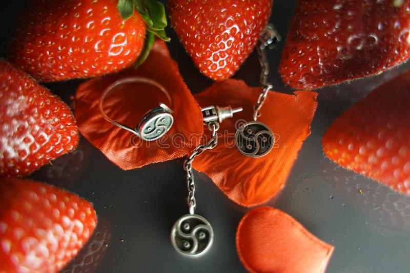 Ring and earrings with the symbol of bdsm lying among the strawberries on the black table top view royalty free stock image