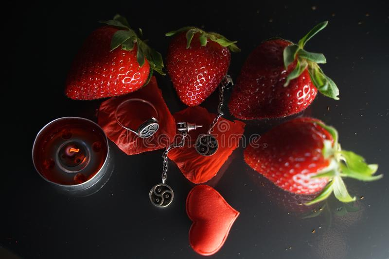 Ring and earrings with the symbol of bdsm lying among the strawberries on the black table top view stock photo