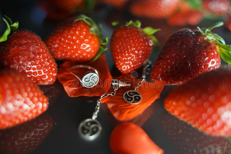 Ring and earrings with the symbol of bdsm lying among the strawberries on the black table top view royalty free stock images