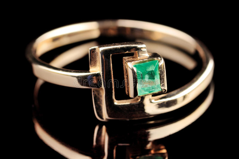 Ring with emerald. On black stock photos