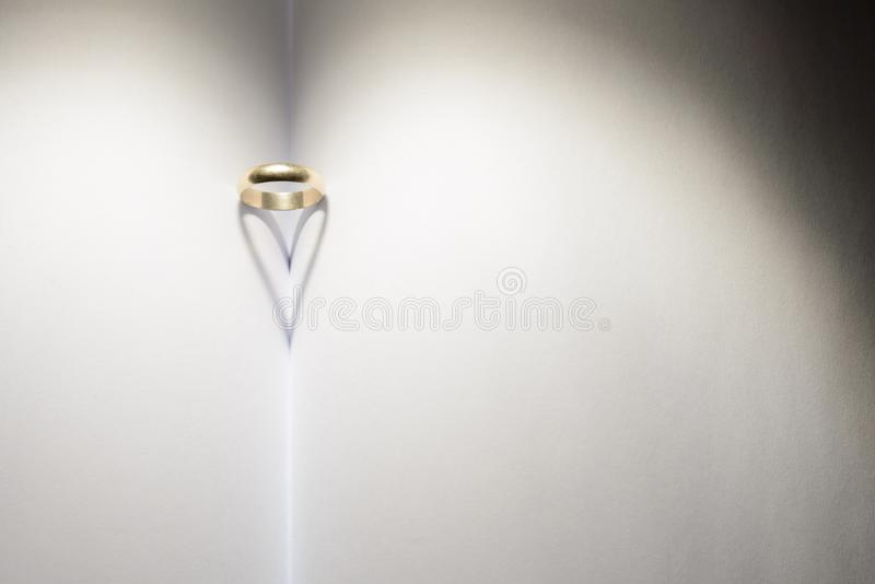 Ring forming a heart of shadow on a book. stock images