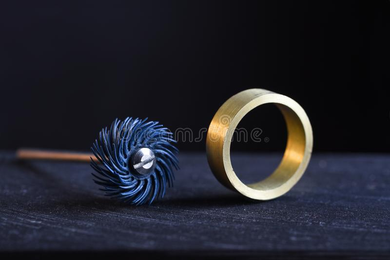 ring from gold and a polishing tool on the workbench of a goldsmith against a dark background with copy space royalty free stock image