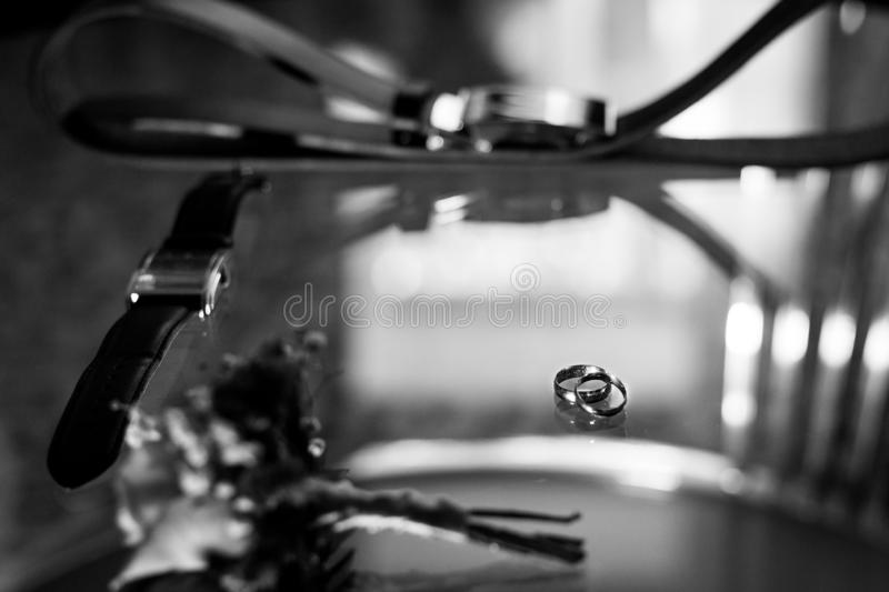 Ring, leather men`s shoes with belt and bow tie. Set of groom accessories on wedding day. Black and white photo royalty free stock image
