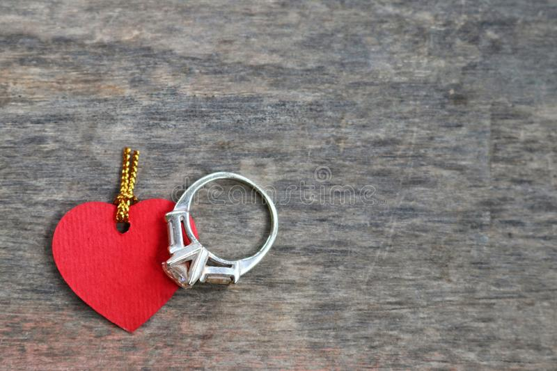 Ring and love. Red heart symbol and ring on old wood for valentine background royalty free stock photography