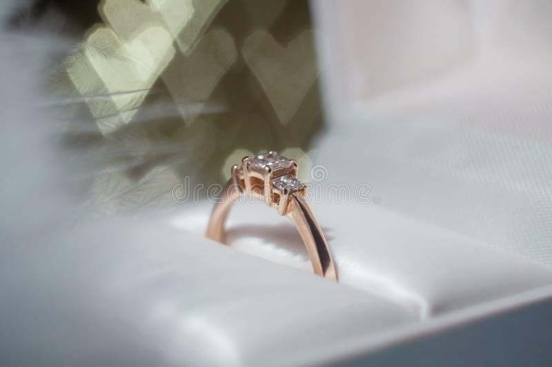 Ring met diamant in een doos tegen de achtergrond van harten De dag van de valentijnskaart `s stock fotografie