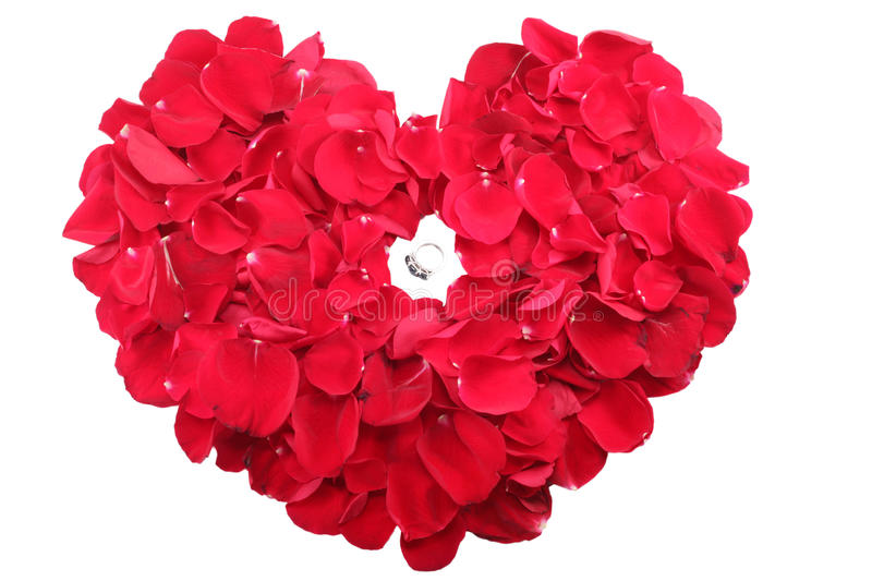 Ring in the middle of a heart of red roses petals. Beautiful ring in the middle of a heart of red roses petals stock photography