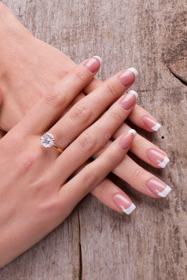 Ring mit einem Diamanten auf einem Finger Schöne französische Maniküre lizenzfreie stockfotos