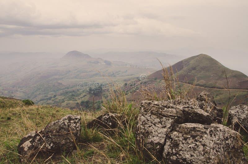 Ring Road en el Camerún, África con las colinas suaves en fondo y las rocas grandes en primero plano en día cubierto fotografía de archivo libre de regalías