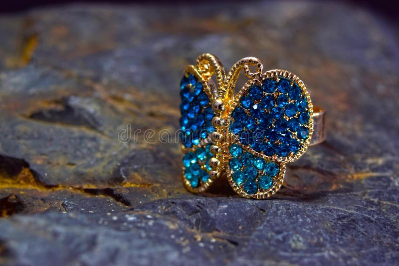 Ring in the shape of a butterfly for a lady on the background. The ring is decorated. With a multicolored gemstone stock photo