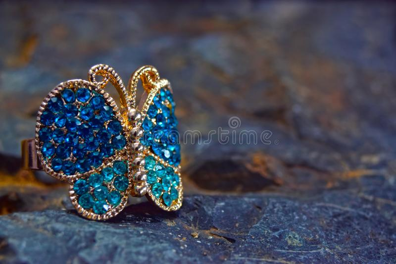 Ring in the shape of a butterfly for a lady on the background. The ring is decorated. With a multicolored gemstone royalty free stock images