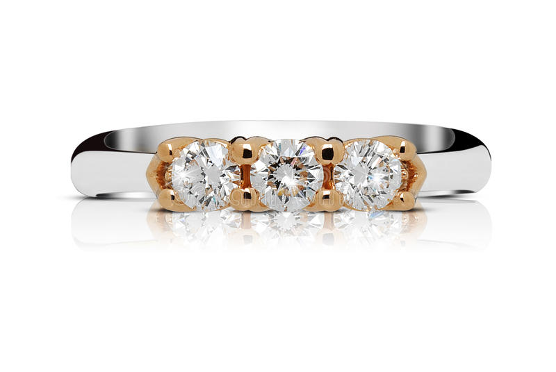 Ring with trilogy of diamonds. Ring with a trilogy of faceted diamonds or clear gemstones mounted in rose gold on a silver or white gold band lying flat on a stock image