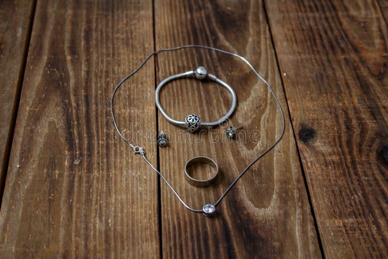 Ring und Armband und Ohrringe und Kette mit Anhänger auf hölzernem Hintergrund lizenzfreie stockfotografie