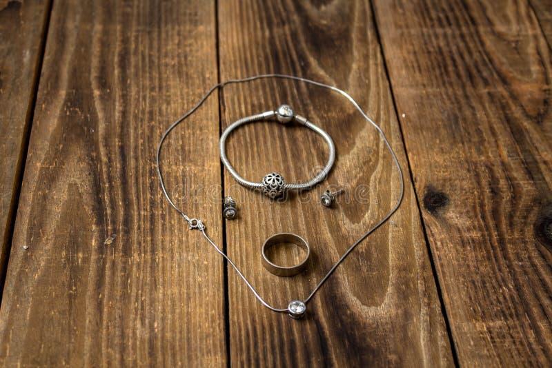 Ring und Armband und Ohrringe und Kette mit Anhänger auf hölzernem Hintergrund lizenzfreie stockbilder